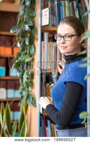 Portrait of clever student in college library