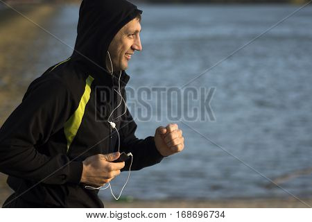 Jogging man is listening music with earphones on the beach.