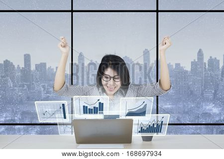Photo of a joyful businesswoman looking at virtual financial chart on the laptop computer in the office