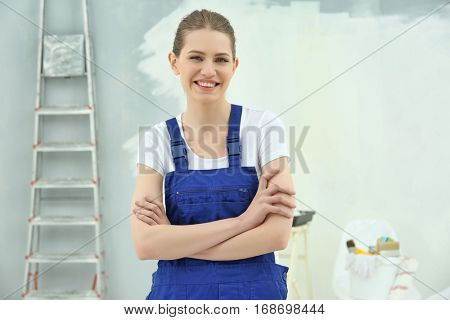 Young female decorator in empty room