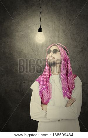 Muslim man wearing muslim clothes looking at light bubble over his head while thinking an idea