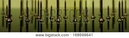 Screws macro photo, yellow background, metal screw