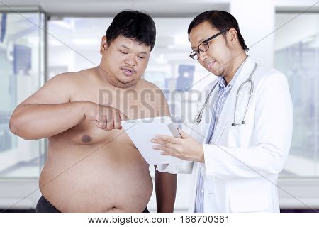 Portrait of overweight patient and his doctor looking at the examination result on the digital tablet in hospital