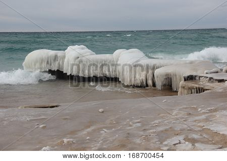 A ice covered breakwater on the shore of Lake Michigan.