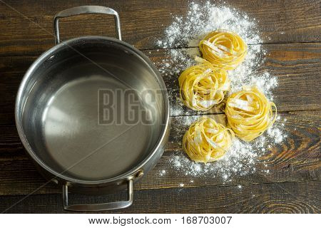 pasta tagliatelle with flour on table and pan clous-up