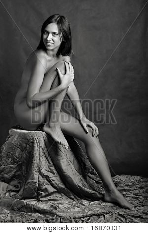 Classical artistic nudity style picture of woman sitting on dark background