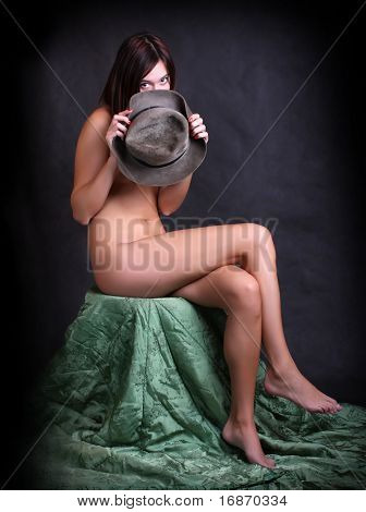 Young naked girl hidden under hat, retro - vintage style studio shot