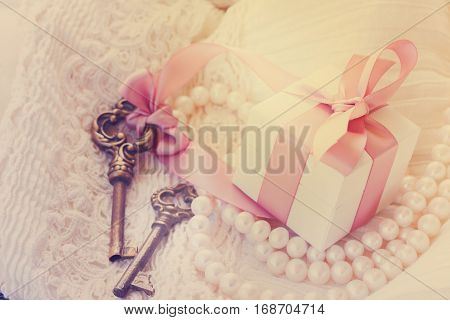 gift box and keys with pearl jewellery and lace, retro toned