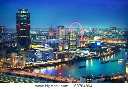 London, UK - December 19, 2015: London at sunset with lights and reflection. View at the Westminster aria, London eye, River Thames, embankment and London bridge