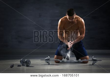Sporty man applying talc powder onto hands prior to doing exercises with barbell indoors