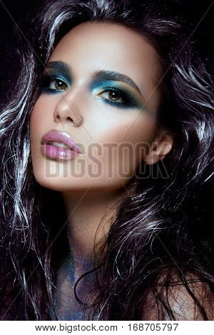 Beautyful girl with blue glitter on her face and body