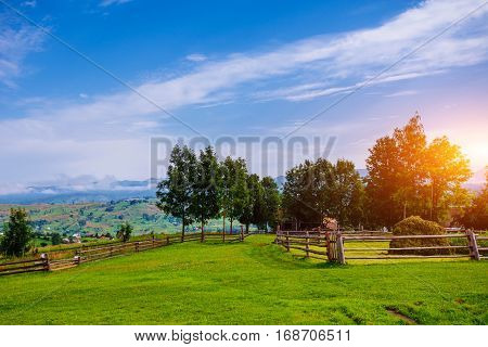 A Wide Angle View of a Wooden Fence Under a Blue Sky with a Beautiful Meadow Blanketed with Wildflowers.