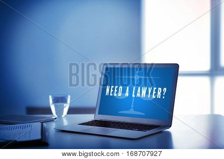 Modern laptop on table. Text NEED A LAWYER? on screen