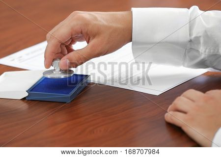 Notary public pressing stamp into ink pad