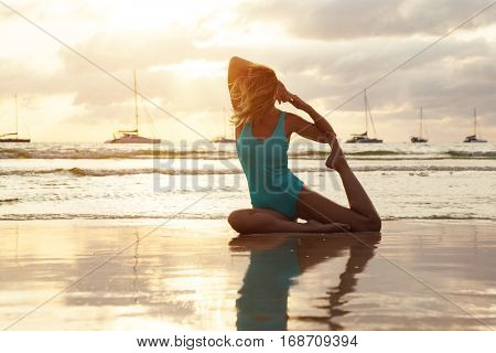 Woman doing yoga exercise on the beach in sunset. Evening meditation near the ocean. Healthy and sport lifestyle. Calm and quiet relaxation scene. Breathing near the water.