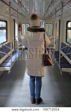 Lonely girl in a hooded jacket standing in a subway train's car