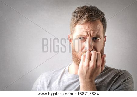 Man with red beard biting his fingers