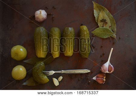 Pickled gherkins in jar, fermented food with spices, view from overhead on wooden table