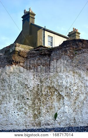 Coastguard cottages above eroding chalk cliffs of Birling Gap East Sussex.