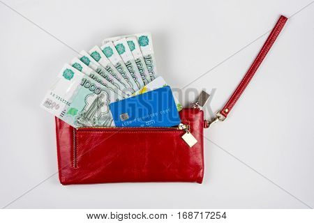 Red Purse From Which Stick Out Money And Credit Cards On A White Background