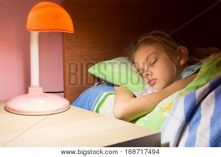 Seven-year girl asleep in bed reading lamp is included on the next table
