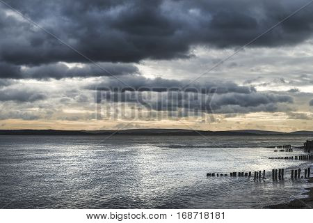 Moody Sea Landscape Looking Across Solent To Isle Of Wight In England With Dramatic Sunset Sky