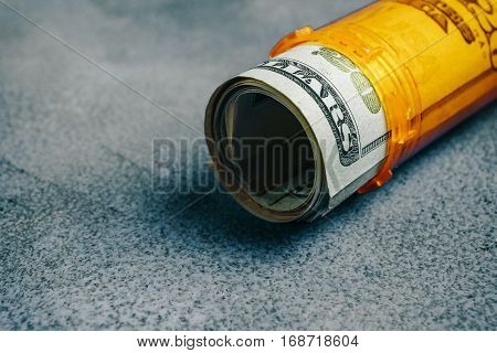 Money Bills in orange pill bottle medical concept with copyspace