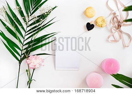 Blanknote green leaves carnation flower pink ombre candles heart macaroons on white. Woman decorating ideas. Negative space for text