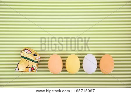 Flat lay horizontal row of colorful eggs and bunny on a greenery striped background. Pastel colors Easter card. Copyspace