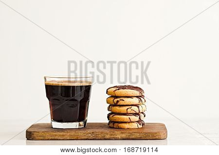 Glass of black coffee and stack of butter cookies with chocolate drizzle on wooden board. White background. Copyspace for text.