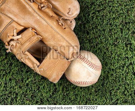 Flat view of old baseball mitt and used ball and on grass surface