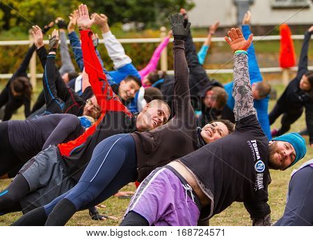 Kiev Ukraine - October 08. 2016. Street workout CrossFit training participants perform stretching at the end of the workout.