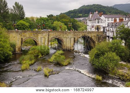 LLANGOLLEN WALES UK - SEPTEMBER 13 2016: The Dee Bridge one of the Seven Wonders of Wales built in 1345 and rebuilt in the 16th century it is the main crossing point over the River Dee or Afon Dyfrdwy in Welsh