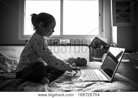 Little girl sitting in bed and playing online games in his bedroom. Black and white shot