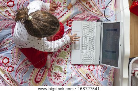 Little girl sitting in bed and playing online games in her bedroom. High angle view
