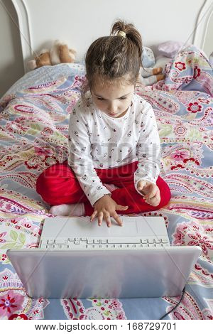 Little girl sitting in bed and playing online games with laptop computer