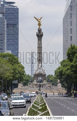 MEXICO CITY MEXICO - JULY 21 2016: The Angel of Independence built in 1910 to commemorate the centennial of the beginning of the War of Independence stands tall the busy boulevard Paseo de la Reforma in downtown Mexico City.