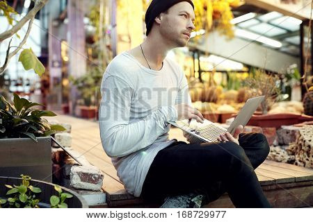 Handsome hipster man portrait dreaming about start-up project working on portable laptop computer. Guy in black hat looking ahead in a park sunny day. Business lifestyle concept