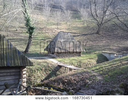 Beautiful old cabin in the woods, sunny sunlight. The architecture of the 19th century showing the simplicity and modesty. Retro style in the Balkans. With a small wooden bridges.