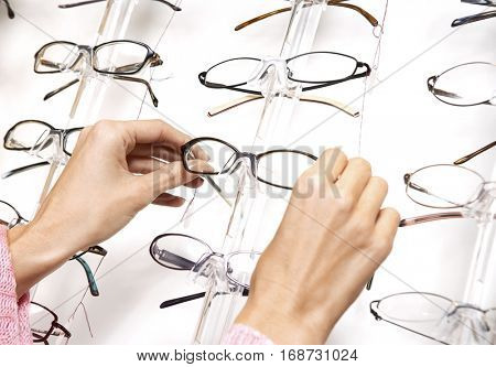Closeup of a female's hands pulling glasses from display rack