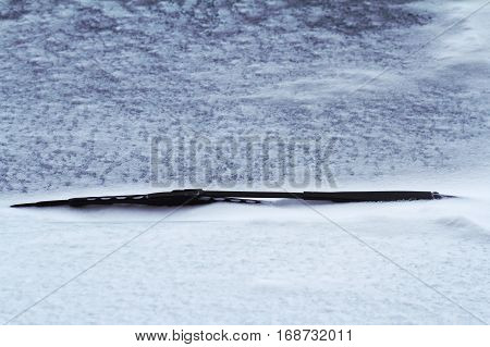 front view close up of a black car frozen windscreen wiper covered in snow in winter time on a city street