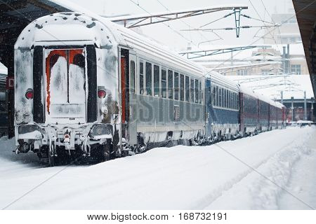 Rear view of the back of a passenger train covered in blizzard snow stopped in railway station winter time
