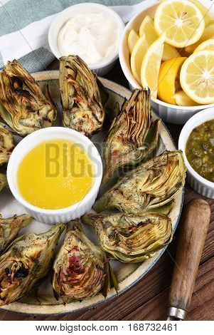 Vertical high angle shot of a plate full of grilled artichokes with butter, mayonnaise and lemons