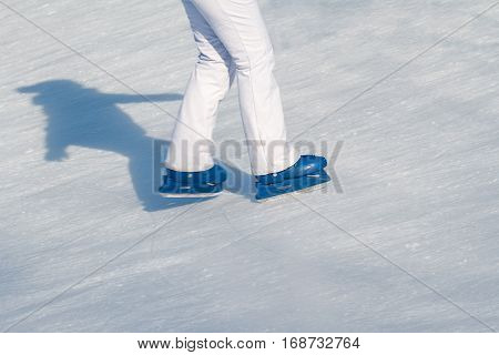 Side view close up of woman in white ski pants and blue iceskates skating on ice rink in wintertime