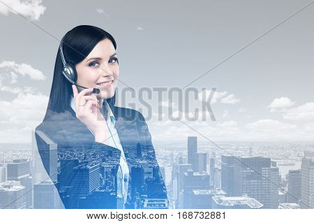 Portrait of a smiling woman with black hair wearing a headset and standing against a city panorama. Mock up. Double exposure