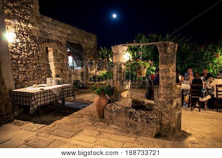 Lecce, Italy - August 10, 2014: Typical Apulian farmhouse on a full moon night.