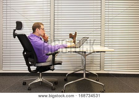 specialist working with laptop in relaxed position with legs on desk
