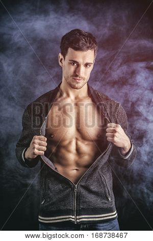 Confident, attractive young man opening vest on muscular torso, ripped abs and pecs. On dark smoky background