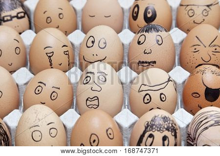 Funny faces on painted on brown eggs arranged in carton
