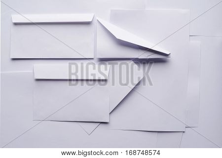 White paper envelope and plane on a background sheet of office paper. Origami